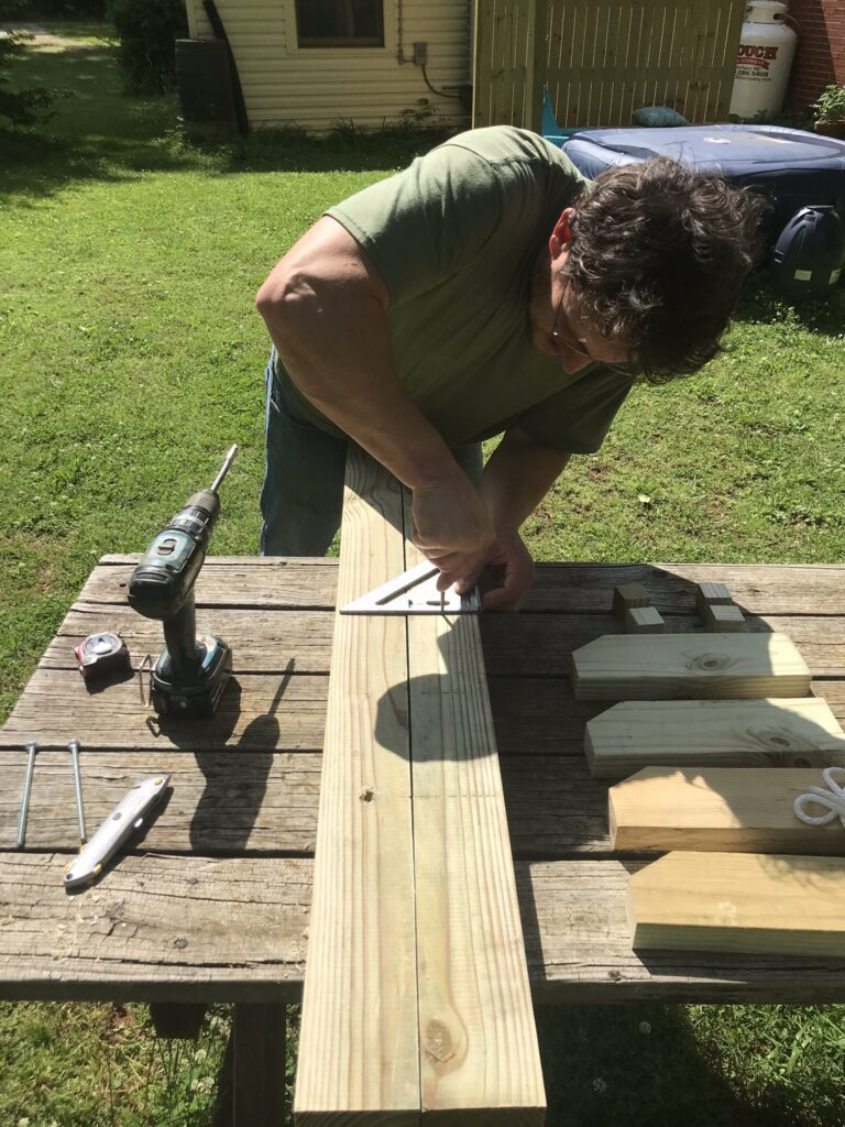 man using square to measure wood for drilling holes